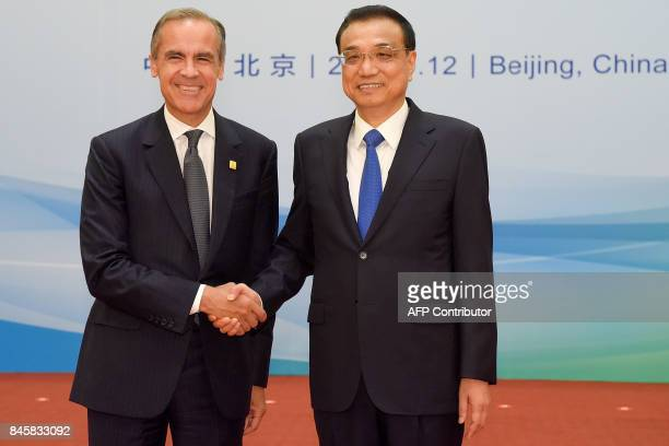 Chairman Mark Carney of the G20's Financial Stability Board shakes hands with Chinese Premier Li Keqiang before The 1+6 Round Table Dialogue meeting...