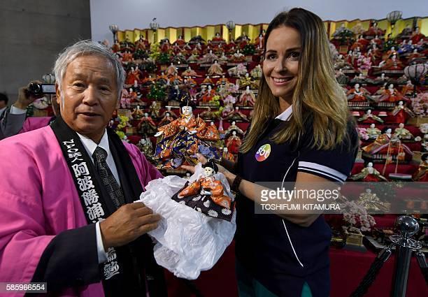 Chairman of Awa Katsuura Idobata Juku Minoru Inai presents dolls to Brazilian TV reporter Claudia Ramos of SBT in front of the big 'HinaMatsuri'...
