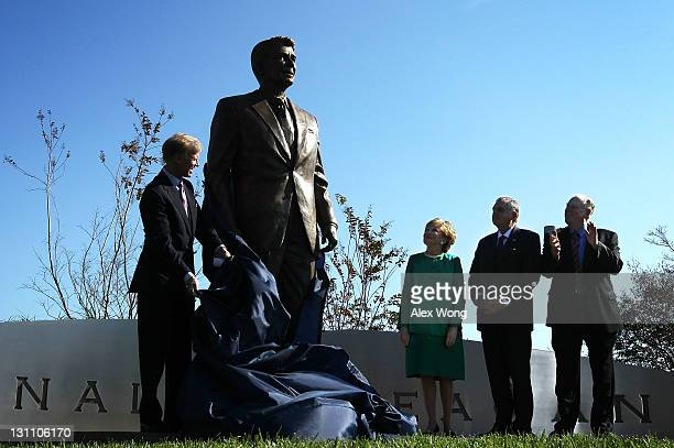Chairman of Board of Ronald Reagan President Foundation Frederick Ryan unveils a statue of former President Ronald Reagan with former Secretary of...