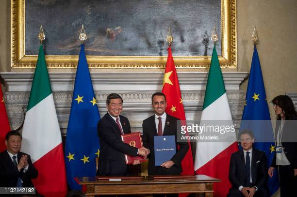 Chairman of China's National Development and Reform Commission He Lifeng and Italian Labor Minister Luigi Di Maio shake hands after the signing...