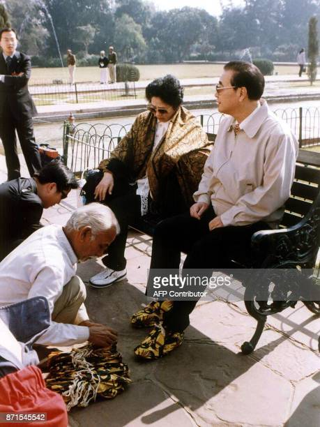 Chairman of China's National People's Congress Li Peng and his wife Zhu Lin are fitted with shoecovers before visiting the Taj Mahal in Agra 14...