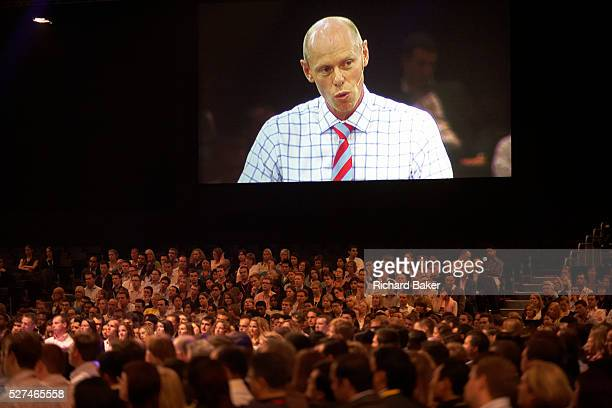 Chairman of Ernst Young Mark Ottey peers down on his employees on a giant screen addressing his loyal audience of E Y staff who have congregated at...