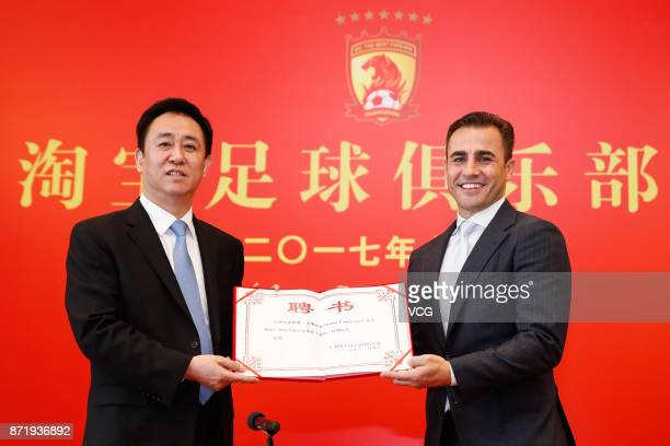 Chairman of Evergrande Group Xu Jiayin and new head coach of Guangzhou Evergrande Fabio Cannavaro pose for photos with the letter of appointment...