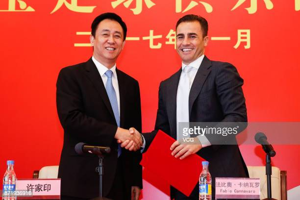 Chairman of Evergrande Group Xu Jiayin shakes hands with new head coach of Guangzhou Evergrande Fabio Cannavaro during a press conference on November...