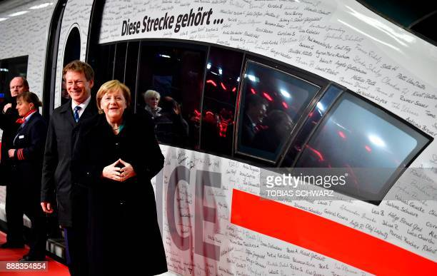 Chairman of German railway operator Deutsche Bahn Richard Lutz and German Chancellor Angela Merkel pose in front of a special ICE high speed train at...