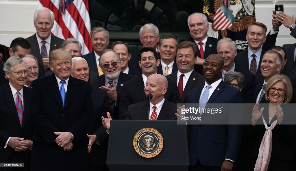 Chairman of House Ways and Means Committee Rep. Kevin Brady (R-TX) (C) as President Donald Trump (3rd L) looks on during an event to celebrate Congress passing the Tax Cuts and Jobs Act with Republican members of the House and Senate on the South Lawn of the White House December 20, 2017 in Washington, DC. The tax bill is the first major legislative victory for the GOP-controlled Congress and Trump since he took office almost one year ago.