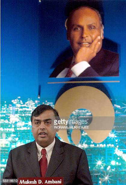 Chairman of India's Reliance Industries Limited Mukesh Ambani stands under a portrait of his late father Dhirubhai Ambani as he addresses...