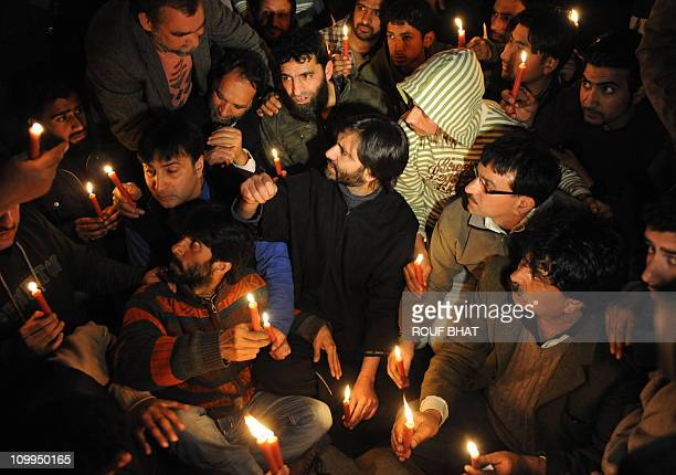 Chairman of Jammu Kashmir Liberation Front Mohammed Yasin Malik sits with supporters during candlelight and torch protest in Srinagar on March 11...