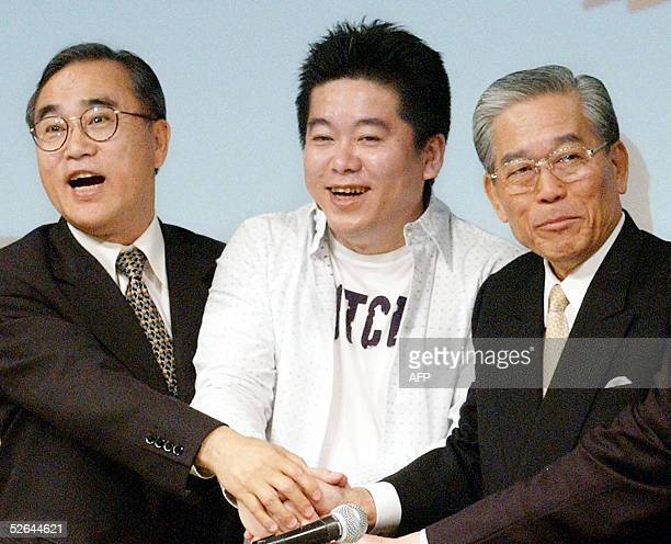Chairman of Japan's largest broadcaster Fuji Television Hisashi Hieda shakes hands with Takafumi Horie president of IT venture Livedoor and and...