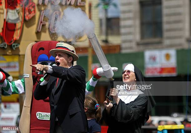 Chairman of Major League Eating George Shea screams to the crowd as a woman dressed as a nun shoots a Tshirt into the crowd before the Nathan's...