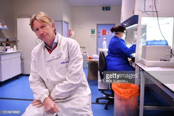 Chairman of Stabilitech Wayne Channon poses as an employee works behind at the Stabilitech laboratory in Burgess Hill south east England on May 15...