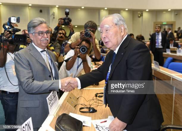 Chairman of Suzuki Motor Corporation Osamu Suzuki shakes hands with Managing Director of Hero MotoCorp Pawan Munjal prior to the inauguration of the...