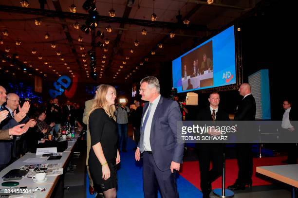 Chairman of the Alternative for Germany farright party Joerg Meuthen and his partner Natalia Zvekic react after he was reelected for two years during...