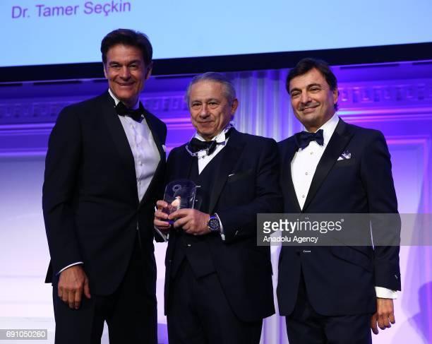 Chairman of the American Turkish Society Murat Koprulu and Dr Mehmet Oz give an award to Dr Tamer Seckin medical director of Seckin Endometriosis...
