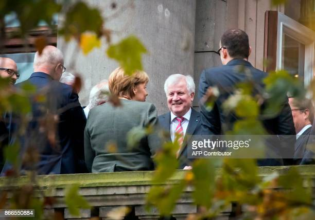 Chairman of the Bavarian Christian Social Union party Horst Seehofer talks with German Chancellor Angela Merkel as they stand on a balcony outside a...