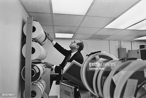Chairman of the Capital National bank Carlos Cordova inspecting a machine in the back office of the bank New York City USA 8th October 1985