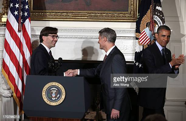 Chairman of the Council of Economic Advisers Alan Krueger shakes hands with economist Jason Furman as US President Barack Obama looks on during a...