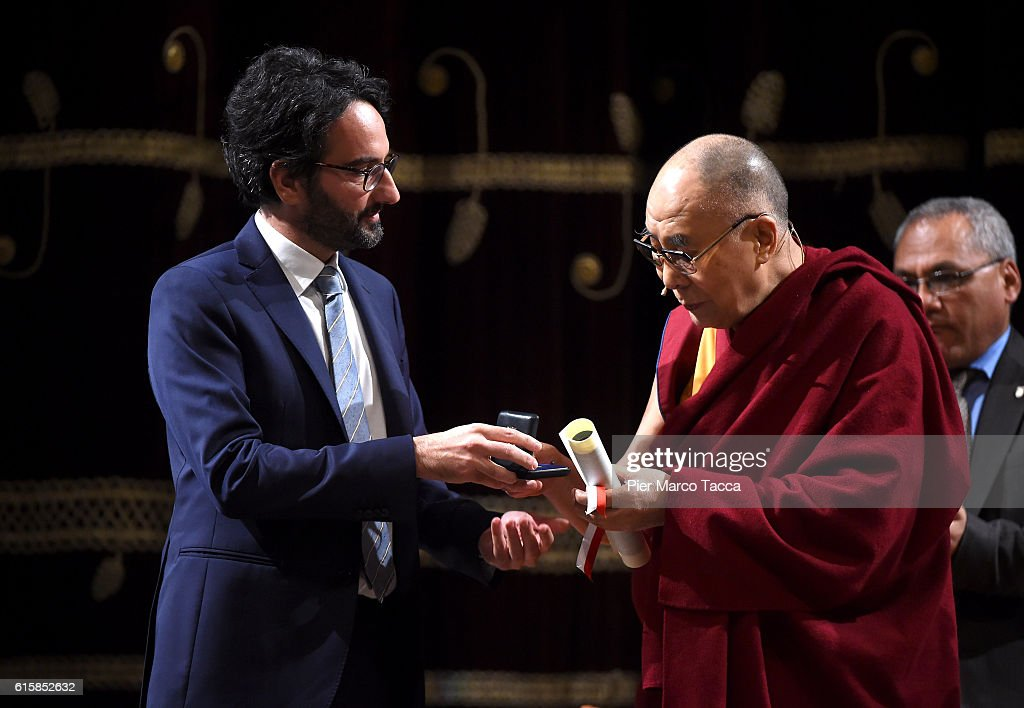 Chairman of the council of Milan Lamberto Bertole gives the certificate of honorary citizenship to the Dalai Lama at the ceremony for honorary citizenship, during the meeting organized by the University Bicocca to the Arcimboldi theater on October 20, 2016 in Milan, Italy. The Dalai Lama spiritual leader of Tibetan Buddhism, starts today the first of a three-day visit and spiritual meetings in Milan.