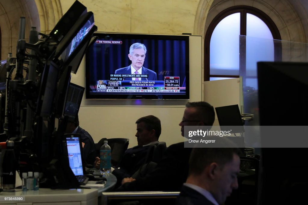 Chairman of the Federal Reserve Jerome Powell is displayed on a television as traders and financial professionals work ahead of the closing bell on the floor of the New York Stock Exchange (NYSE) June 13, 2018 in New York City. Following news today that the Federal Reserve raised interest rates a quarter percentage point, the Dow Jones Industrial Average was down 119 points at the close.