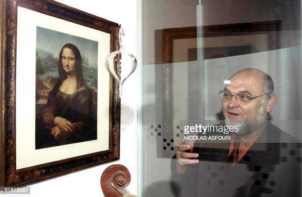 Chairman of the French Communist Party Robert Hue watches a moustachioed Mona Lisa by dadaist painter Marcel Duchamp lent out by his party for the...