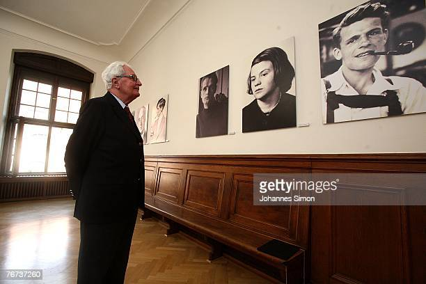 Chairman of the German Social Democrats HansJochen Vogel looks at photographs of the White Rose movement members Alexander Schmorell Hans Scholl...