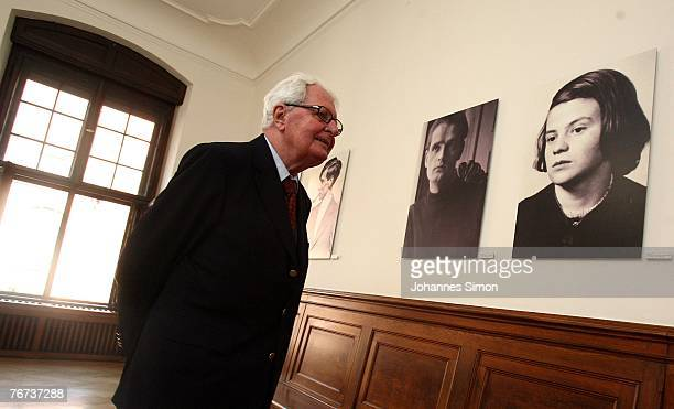 Chairman of the German Social Democrats HansJochen Vogel looks at photographs of the White Rose movement members Alexander Schmorell Hans Scholl and...
