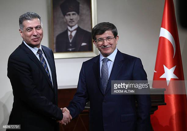 Chairman of the Iraqi Turkmen Front Arshad al-Salihi shakes hands with Turkish Foreign Minister Ahmet Davutoglu after a press conference in Ankara...