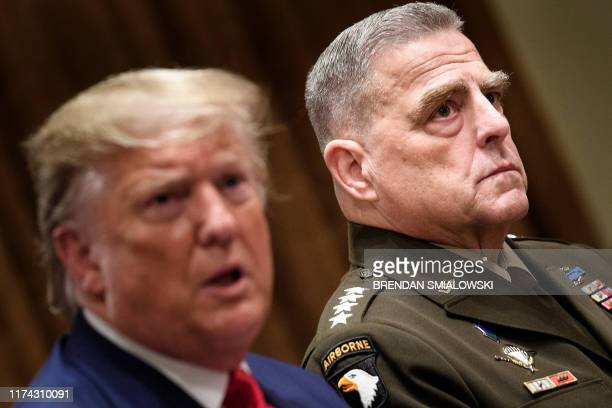 Chairman of the Joint Chiefs of Staff Army General Mark A Milley listens while US President Donald Trump speaks before a meeting with senior military...