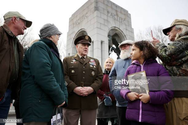 Chairman of the Joint Chiefs of Staff Gen Mark Milley talks with three generations of veterans from one family following a ceremony marking the 75th...