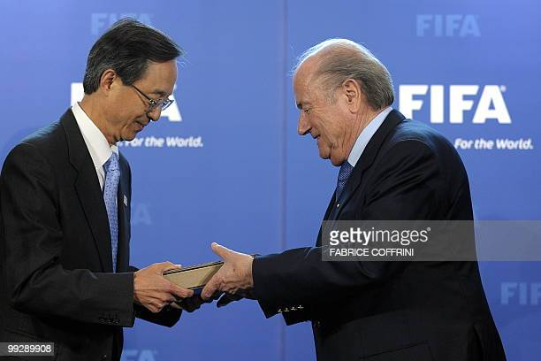 Chairman of the Korean bid committee Han SungJoo delivers to FIFA president Sepp Blatter the World Cup bid books during an official handover ceremony...
