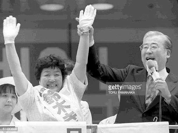 Chairman of the opposition Social Democratic Party Sadao Yamahana raises the hand of SDP candidate Kikuko Suzuki during a campaign rally for general...