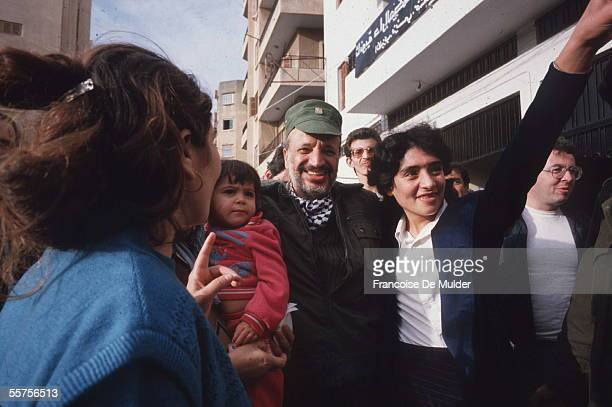 Chairman of the Palestinain Liberation Organization and later president of the Palestinian Authority Yasser Arafat smiles as he walks down a street...