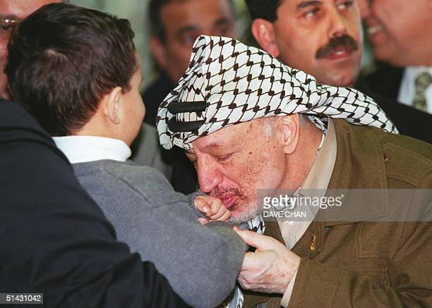 Chairman of the Palestine Liberation Organization, Yasser Arafat, kisses the hand of four-year-old Adam Awada 24 March 1999 upon arriving at Ottawa...