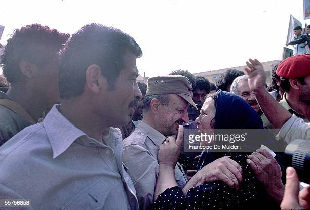 Chairman of the Palestinian Liberation Organization and later president of the Palestinian Authority Yasser Arafat embraces a woman in a crowd...