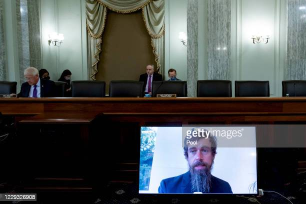 Chairman of the Senate Commerce, Science, and Transportation Committee Roger Wicker listens as CEO of Twitter Jack Dorsey appears on a monitor as he...
