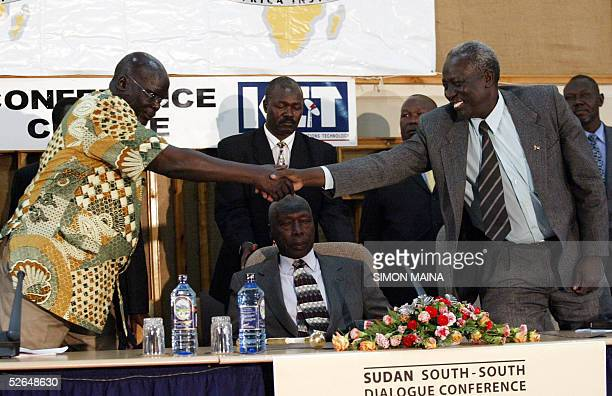 Chairman of the Sudanese People Liberation Movement Army John Garang shakes hands with Sudanese second vice president Prof Moses Machar as former...