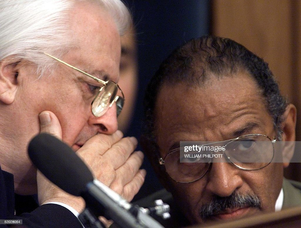 Chairman of the US House Judiciary Committee Henry Hyde, R-IL (L), confers with Democratic committee leader John Conyers (D-MI) during the panel's impeachment inquiry of US President Bill Clinton 12 December on Capitol Hill in Washington, DC. The sharply divided congressional panel approved the fourth of four articles of impeachment against Clinton that will now go to the full House for a vote next week.