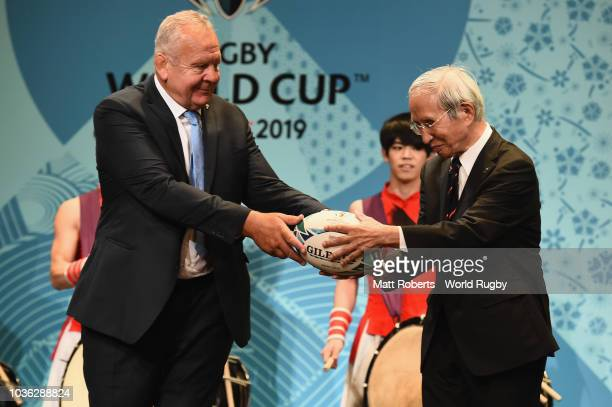 Chairman of the World Rugby via Getty Images Bill Beaumont passes the ball to Chairman of the Japan Rugby Football Union Tadashi Okamura on stage...