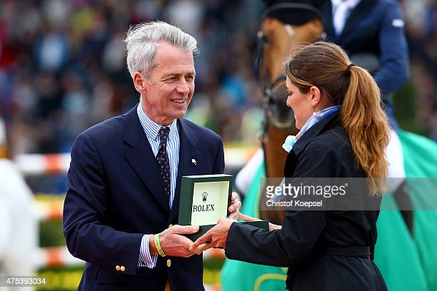 Chairman Peter Streit of Rolex Germany gives back the Grand Prix trophy during toe podium of the Rolex Grand Prix jumping competition of the 2015...