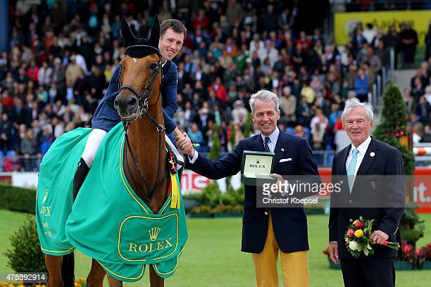 Chairman Peter Streit of Rolex Germany hands out the trophy to winner Scott Brash of GreatBritain rides on Hello Sanctos with Carl Meulenbergh...