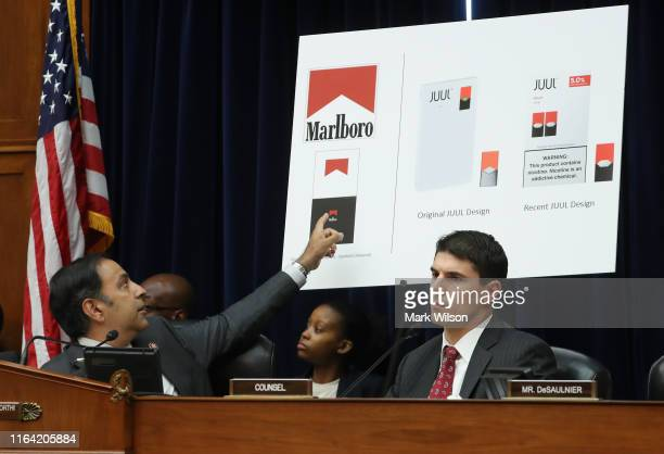 Chairman Raja Krishnamoorthi points to a poster showing similarities between Marlboro cigarette ads and JUUL vaping paraphernalia, during a House...