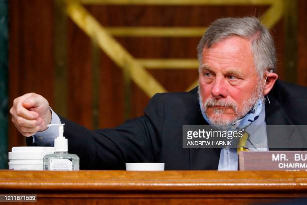 Chairman Richard Burr, R-NC, reaches for hand sanitizer at a Senate Intelligence Committee nomination hearing for Rep. John Ratcliffe, R-TX, on...