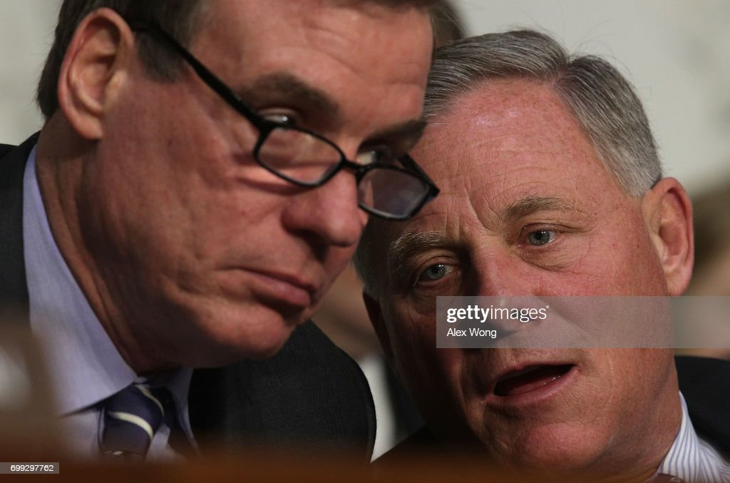 Chairman Sen. Richard Burr (R-NC) (R) talks to Vice Chairman Sen. Mark Warner (D-VA) (L) during a hearing before the Senate (Select) Intelligence Committee June 21, 2017 on Capitol Hill in Washington, DC. The committee held a hearing on 'Russia's cyber efforts against our election systems in 2016, our response efforts, potential threats to our 2018 and 2020 elections, and how we are postured to protect against those threats.'