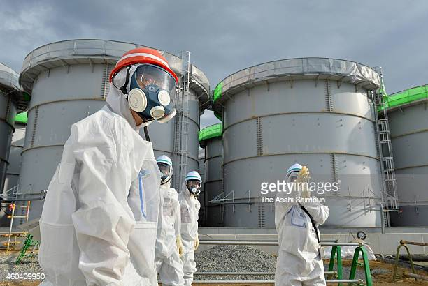 NRA Chairman Shunichi Tanaka inspects storage tanks holding water contaminated with radioactive substances at the Fukushima Daiichi Nuclear Power...