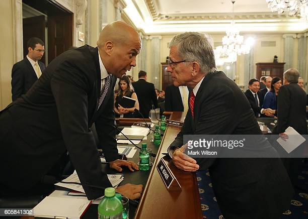 Chairman Tom Wheeler talks with Sen Cory Booker before the start of a Senate Commerce Science and Transportation Committee hearing on Capitol Hill...
