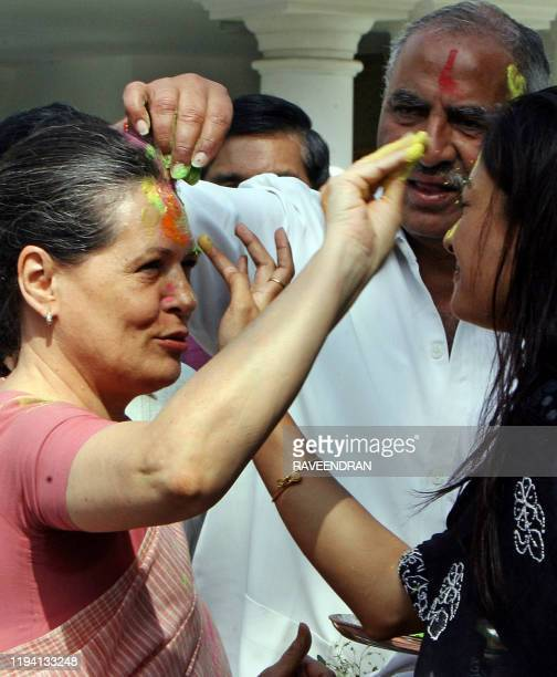 "Chairperson of the Congress-led UPA government and Congress Party President Sonia Gandhi is daubed with festive ""Holi"" colours from party supporters..."