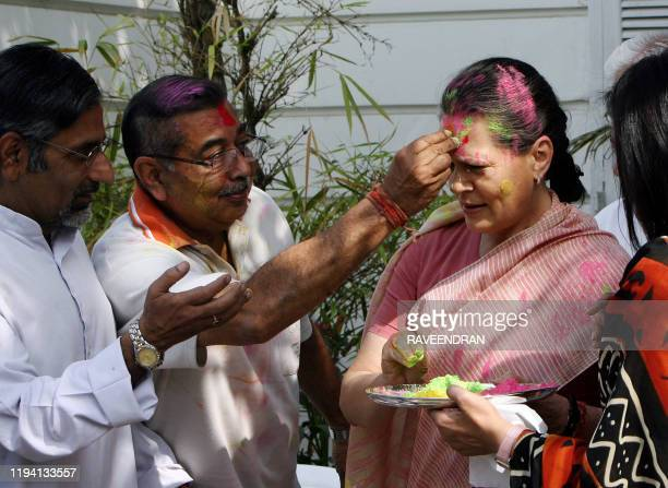 """Chairperson of the Congress-led UPA government and Congress Party President Sonia Gandhi is daubed with festive """"Holi"""" colours from party supporters..."""