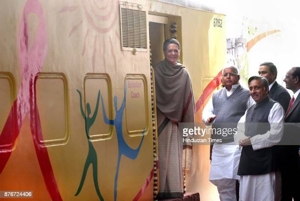 Chairperson of United Progressive Alliance Sonia Gandhi stands on the footplate as Railway Minister Lalu Prasad looks on during the launch of the Red...