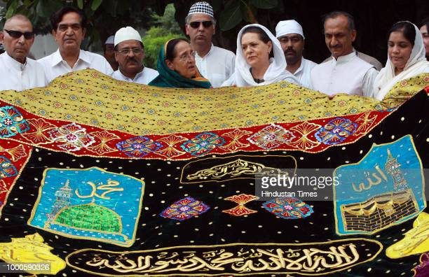 Chairperson of UPA government and Congress Party President Sonia Gandhi along with Congress leaders and devotees stands beside a large shawl [...