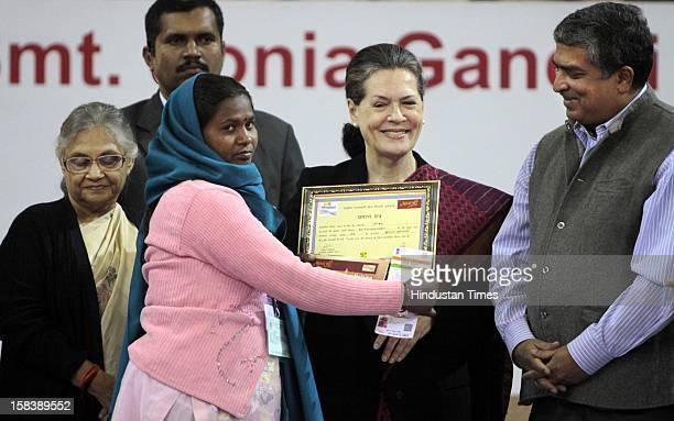 UPA chairperson Sonia Gandhi Delhi Chief Minister Sheila Dikshit and UIDAI Chairman Nandan Nilekani giving away an Aadhar enabled card during the...